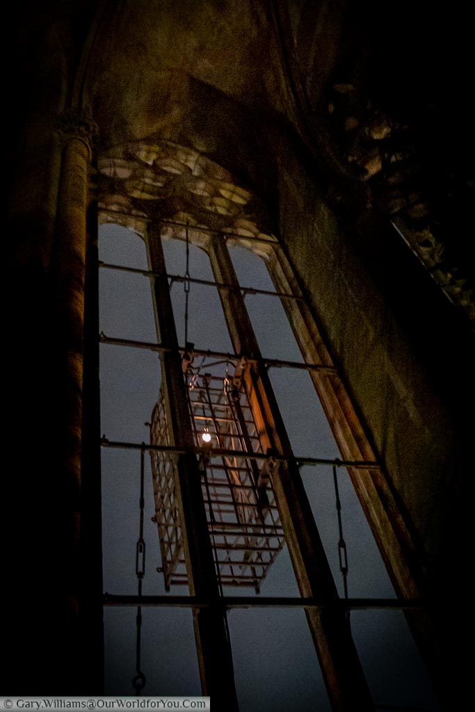 Focusing on one of the Anabaptist cages inside the bell tower of St. Lamberti Church at night.  The only light is a single bulb in the cage and a little moonlight.