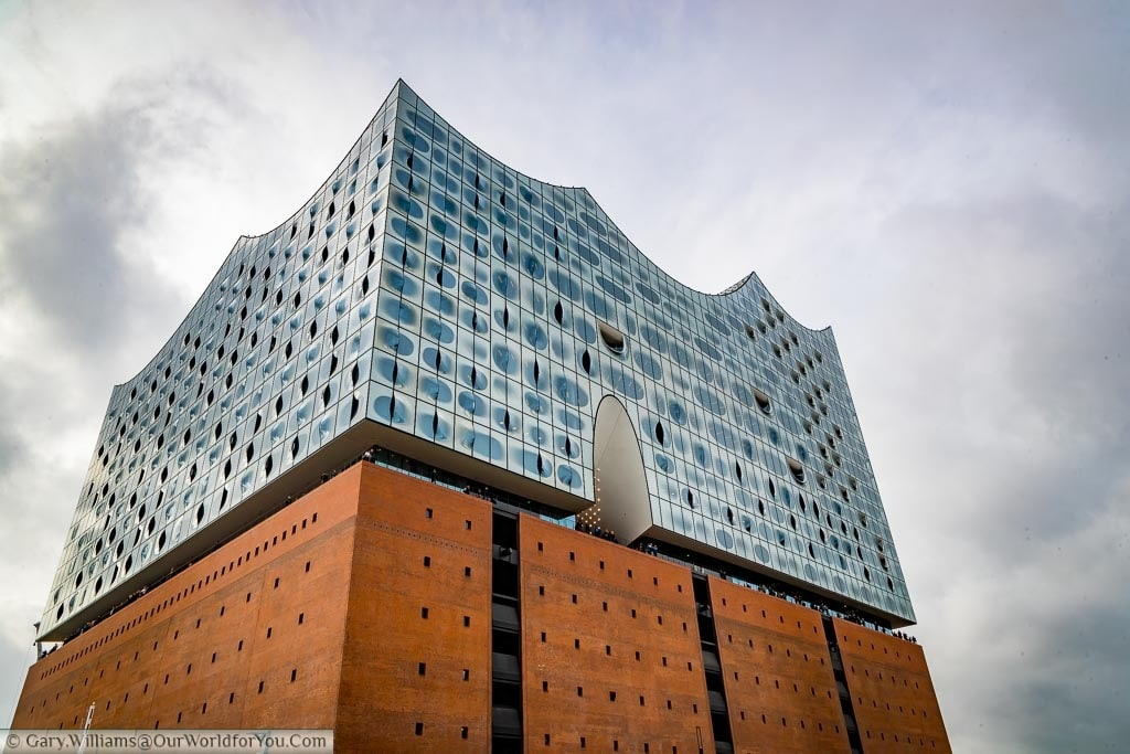 The Elbphilharmonie from ground level looking at the red brick base and the unique glass upper levels of this impressive concert hall.