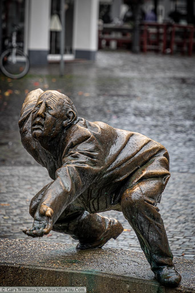A brass statue of old man, bent over, hand out, begging for loose change next to Circle of Money fountain.
