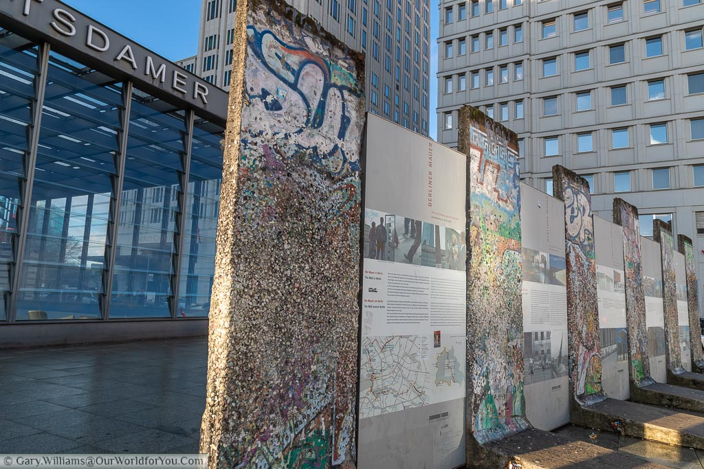 Sections of the Berling Wall, intersected with storyboards, by Potsdamer Platz underground station.