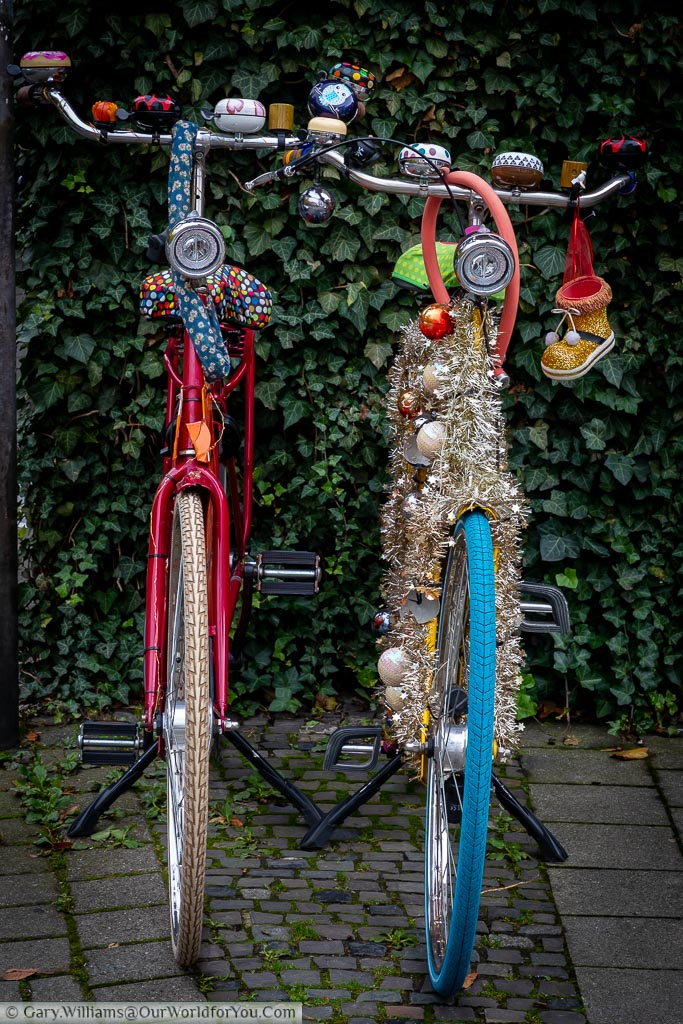 Two traditional bicycles decorated with baubles, tinsel and other ornaments parked up on their stands on the street side.  Münster has German's capital of bicycles with more bikes than people.