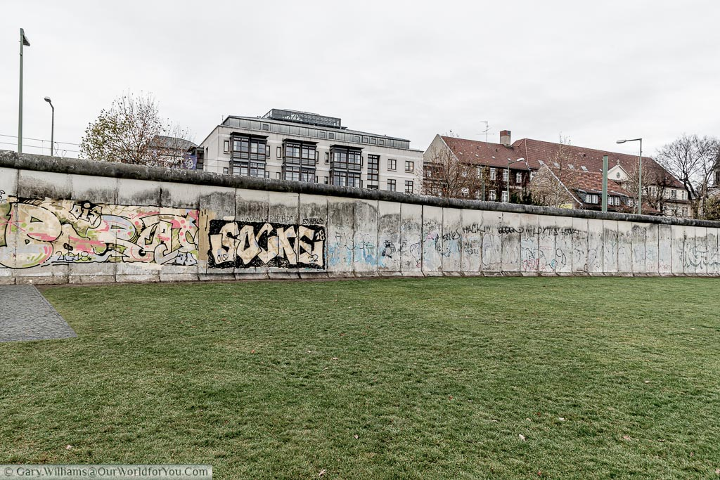 "A grey and bleak view of the Berlin Wall from the grass area that's was once known as the ""Death Strip"""