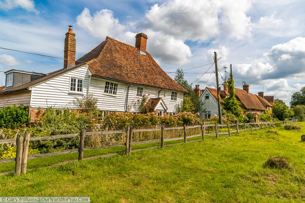 A white timber clad cottage alongside the churchyard on a sunny day