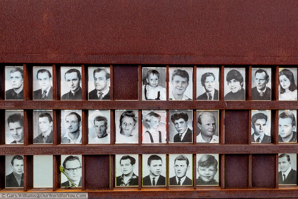 An oxidised metal memorial picture frame of 3 rows of portraits of those who died trying to cross the Berlin Wall.