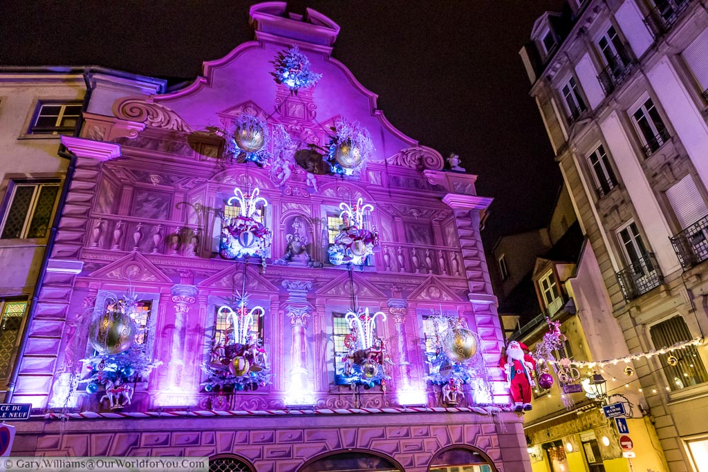 The ornately decorated gable end of a historic building brightly lit in pink with candy canes, reindeers, baubles and even Santa.