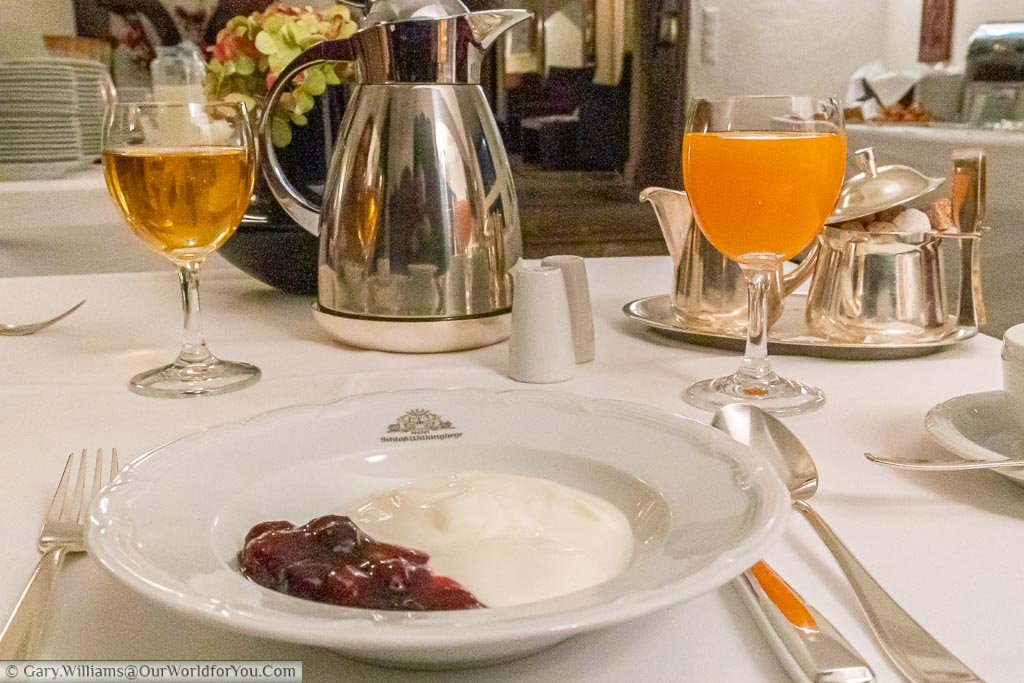 A breakfast course at Schloss Wilkinghege of natural yoghurt and cherry compote, with a glass of orange juice.  The breakfast selection is extensive and of the finest quality.