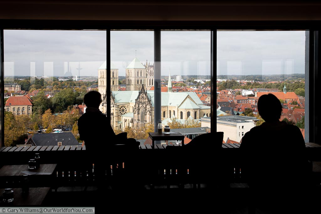 The silhouette of two women in Café 1648 enjoying the 12th-floor panoramic view of St.-Paulus-Dom.