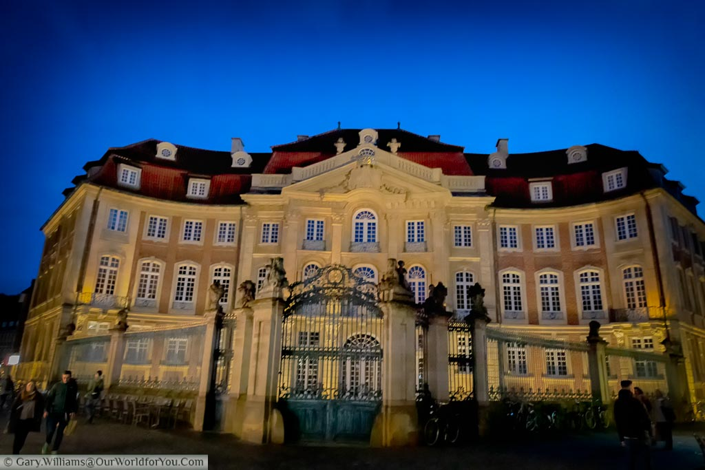 The Baroque Erbdrostenhof palace at dusk under a blue sky.  The lit sandstone building stands imposingly over Salzstraße and Ringoldsgasse.