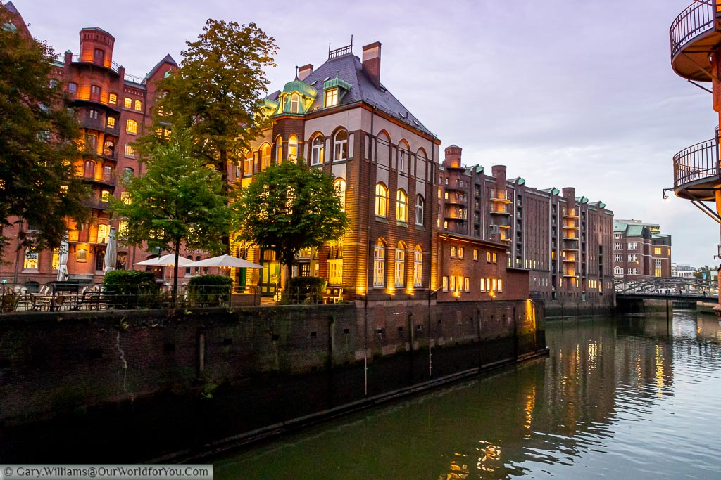 The Wasserschloß building in the Speicherstadt warehouse district of Hamburg at dusk.