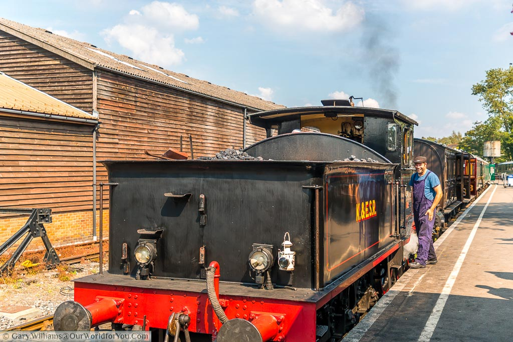 The back of a steam train with dark smoke coming from its chimney and the driver preparing to get on his way on a bright sunny day