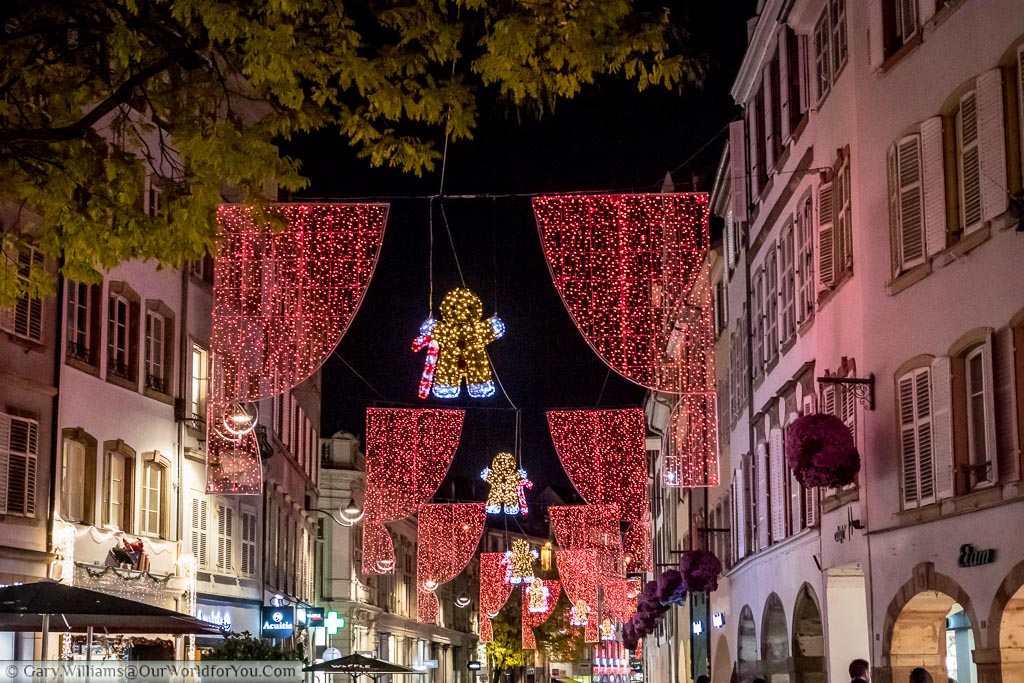 The street lights at Christmas along Place Gutenberg this year are gingerbread men holding candy canes between red curtains.  They extend down the street as far as the eye can see.
