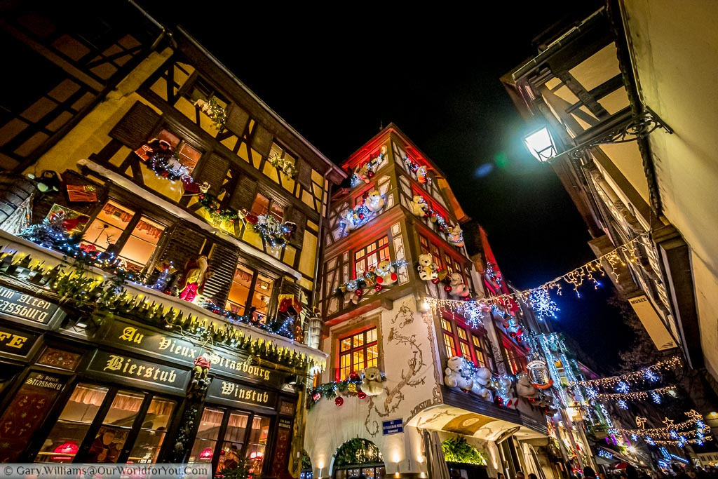 Looking up along Rue du Maroquin at night full of traditional half-timbered buildings that look extra special at Christmas.  Lights hang between the buildings and every window decorated with lights and one building, teddy bears.