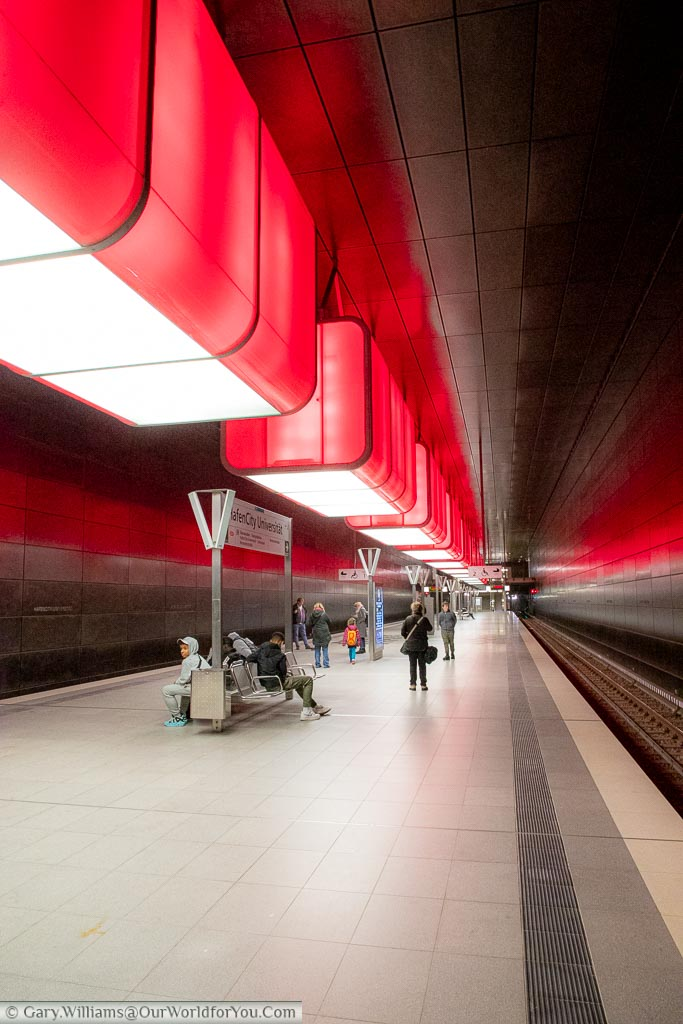 Looking along the platform of  HafenCity Universität U-Bahn station where the overhead lighting is projecting Has now transitioned to red lighting.