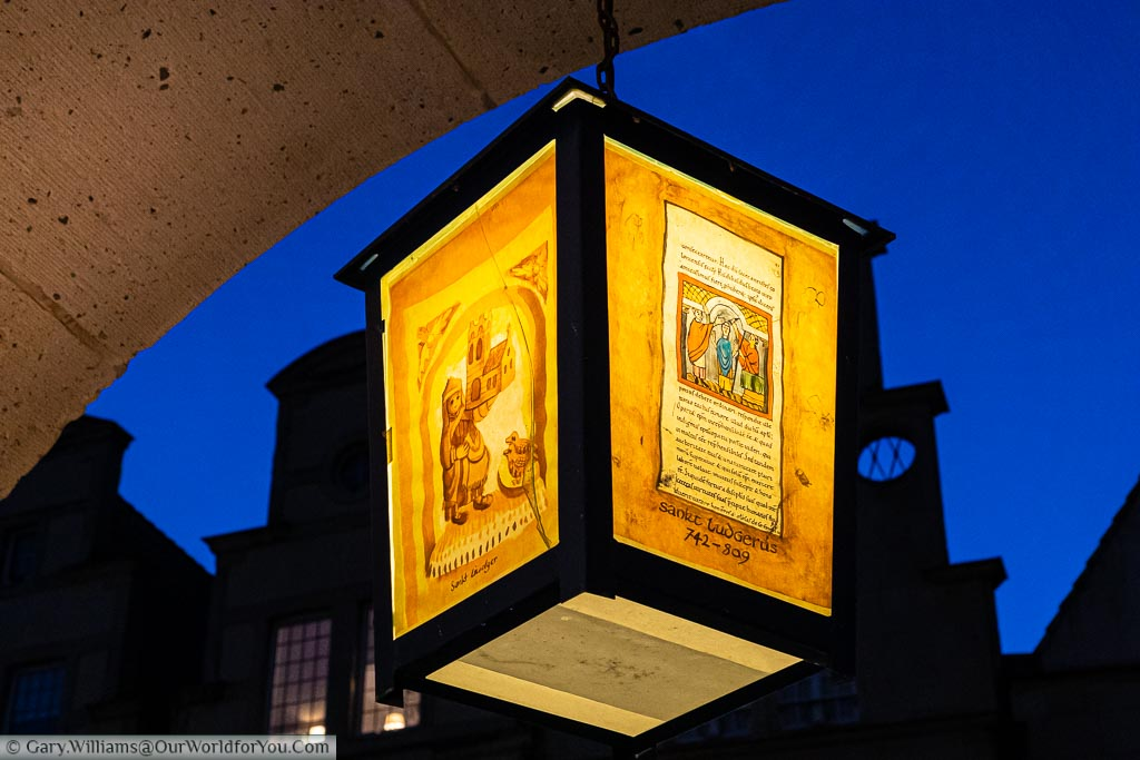 A lit orange lantern, handing from an arch in Prinzipalmarkt, depicting scenes from historic German tales against the deep blue of dusk and the rooftops of the merchants' buildings.