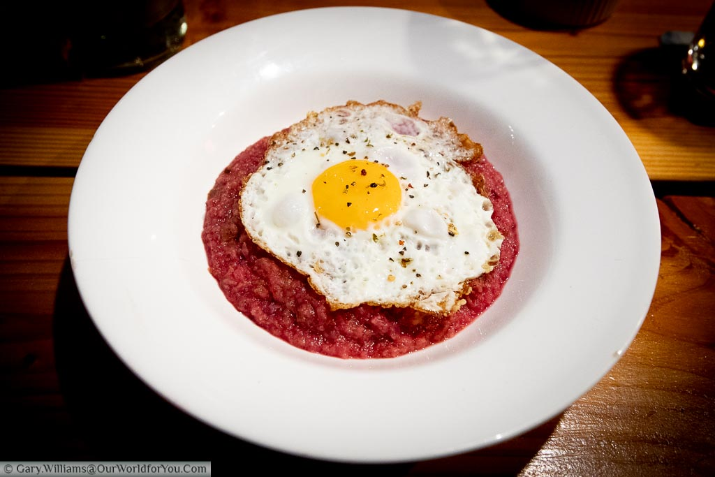 A bowl of Labskaus. A traditional corn beef and beetroot hash with a fried egg placed on top.  This is a regional speciality of Hamburg.