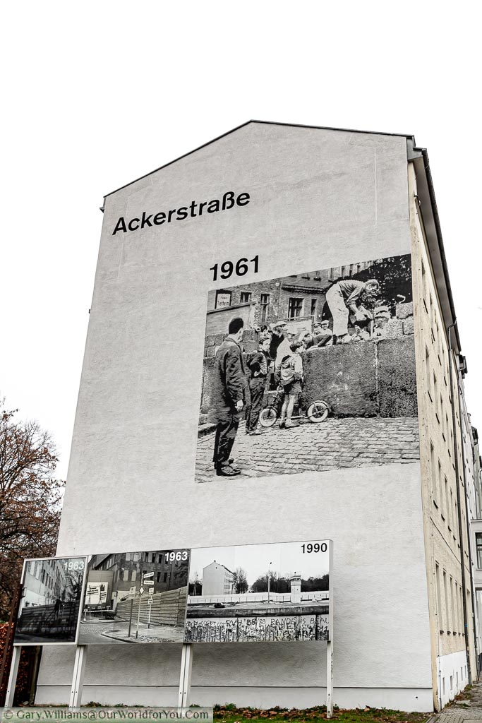 A blown-up picture on the end of a building block depicting the scene of the Berlin Wall in 1961.