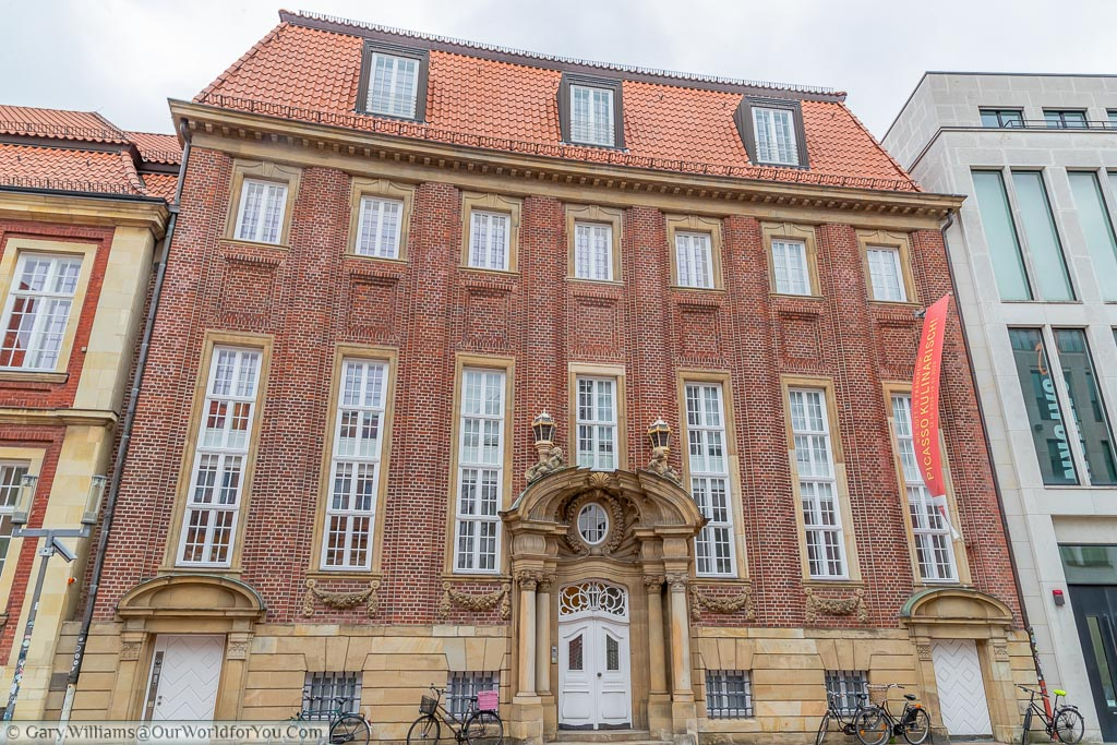 The red brick building houses the Pablo Picasso museum extension.  The facade is grand in stature, but relatively plain except for the baroque style front door.