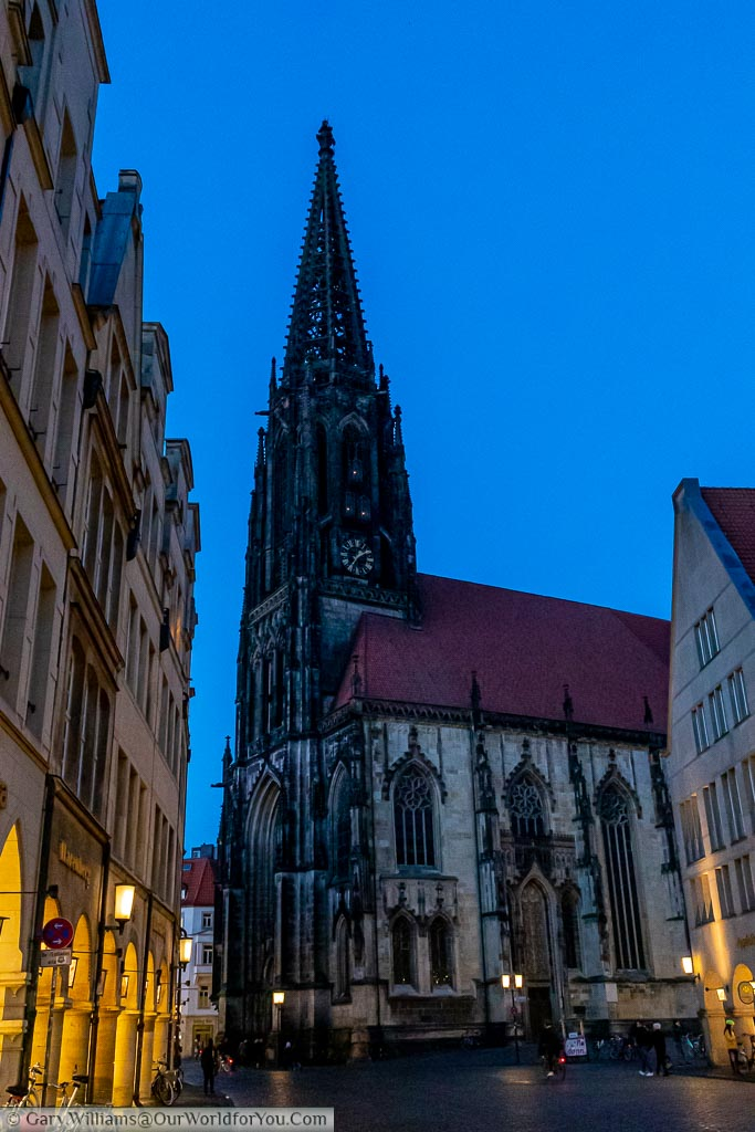 The St. Lamberti Church at dusk.  Close inspection shows the 3 lights installed in the Anabaptists cages attached to the spire, above the clock.