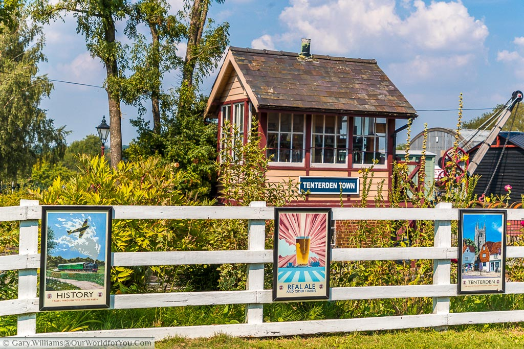 The signal box at Tenterden town steam railway with a white picket fence in front displaying posters of a bygone era.