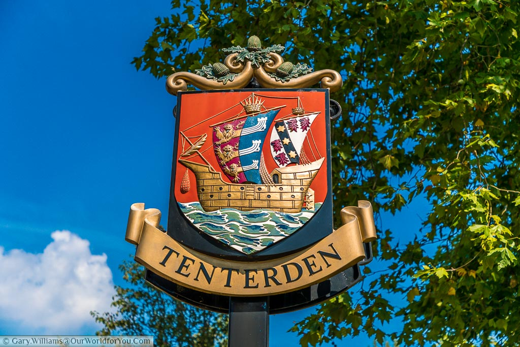 The Tenterden town sign depicting a galleon on the open sea with sails displaying the coat of arms of the cinque ports which are 3 heraldic lions that merge into 3 long boats.