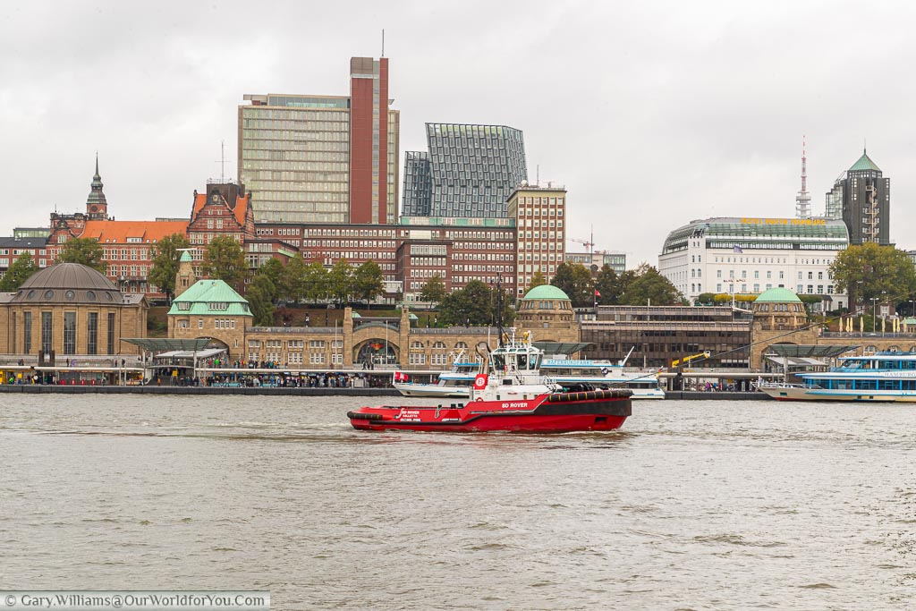 A red tug travelling along the Elbe River in front of the landing stages, against the backdrop of the St Pauli district of Hamburg.