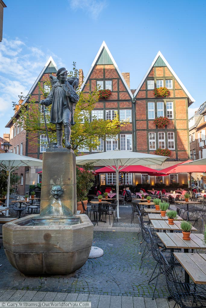 A statue of a historical travelling merchant over a water fountain surrounded by tabes & chairs of the nearby reasturant, bars & cafes.