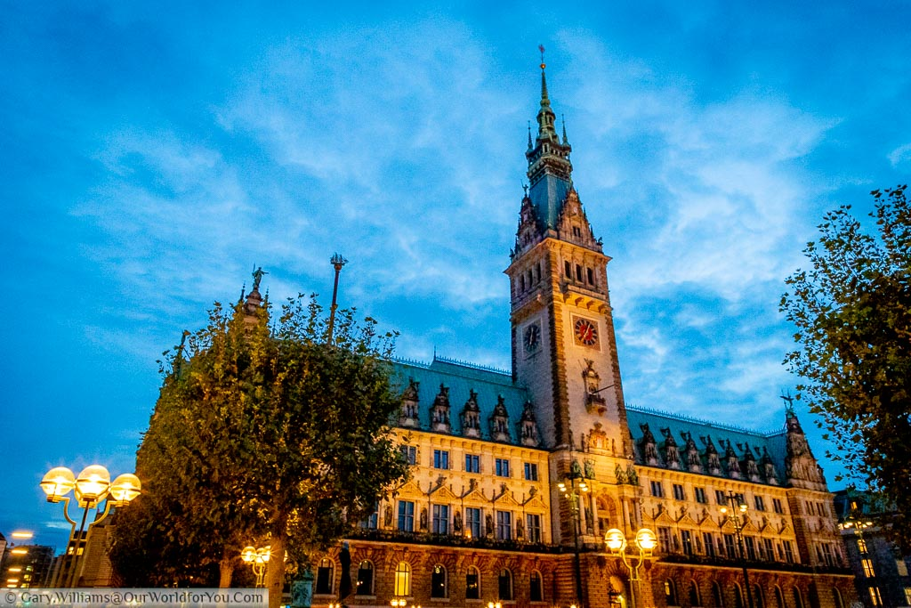 The floodlit gothic styled Rathaus of Hamburg under the blue sky of dusk, with street lights twinkling in the foreground.
