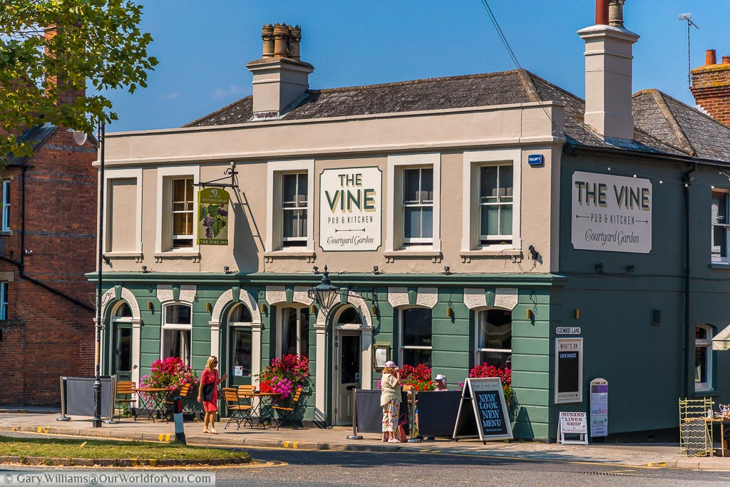 The Vine pub on the High Street freshly painted in a green and cream colour scheme. Decorated with flower arrangements and tables and chairs outside.
