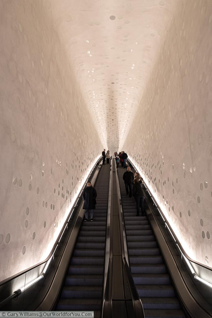 Looking up for the dramatic white tiled escalator to the first stage of the Elbphilharmonie building.