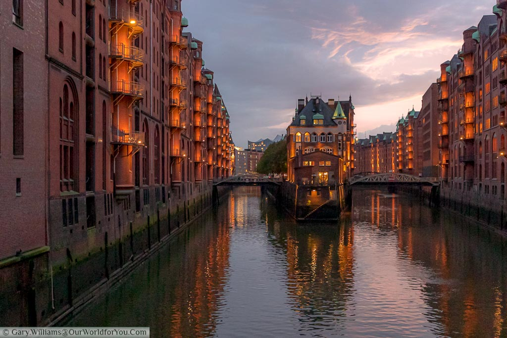A view of the Speicherstadt warehouse district of Hamburg at dusk.  You look down the canal to the water castle with red brick buildings on either side with illuminated balconies.