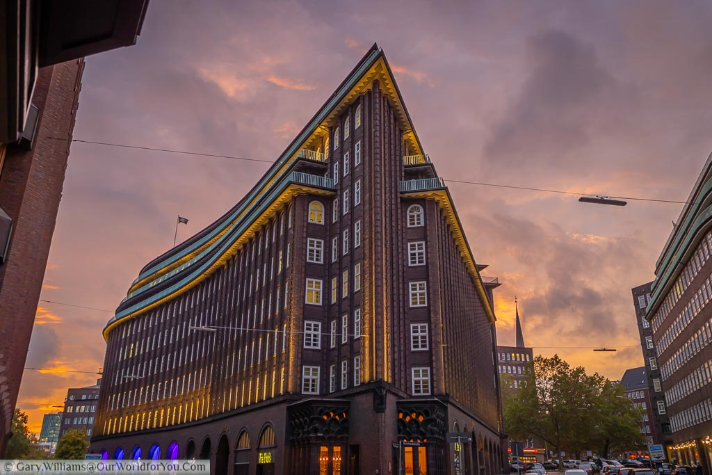 The sharp end of the Chilehaus office building at dusk under mauve to purple skies.  This stylish 10-storey office block looks like a vision of the future as seen from the 1920s.