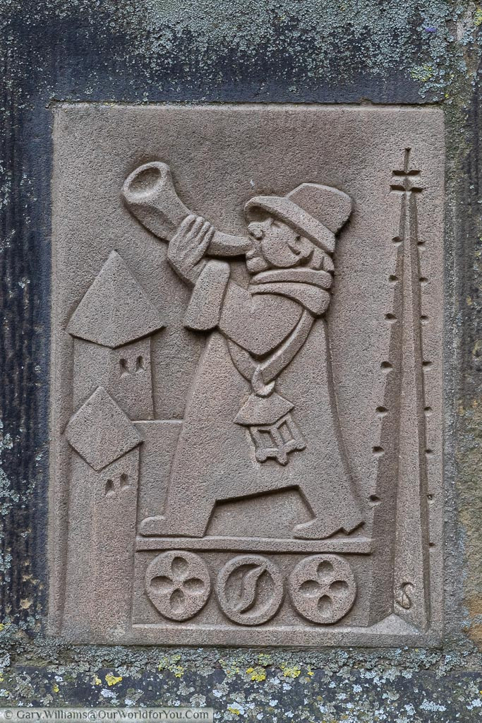 The stone plaque at the base of the bell tower of St. Lamberti church depicting the tower warden.