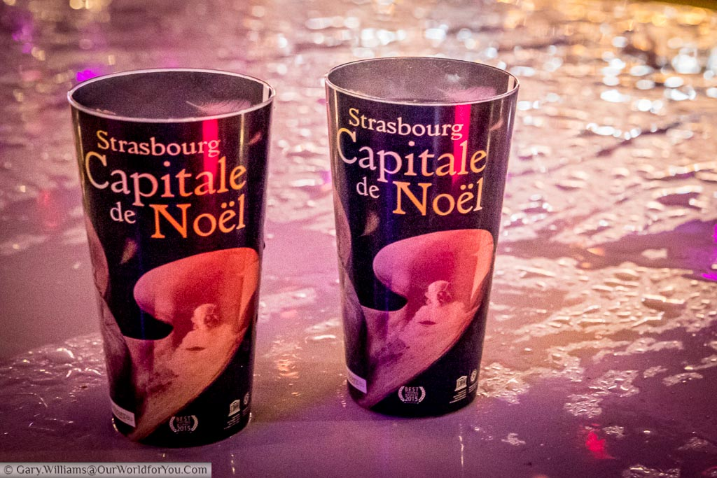 Two plastic beakers of vin chaud on the top of a wet tabletop at one of the Christmas Markets.  The cups are decorated  with angels and labelled with the cities Christmas tag - Strasbourg, Capitale de Noel.