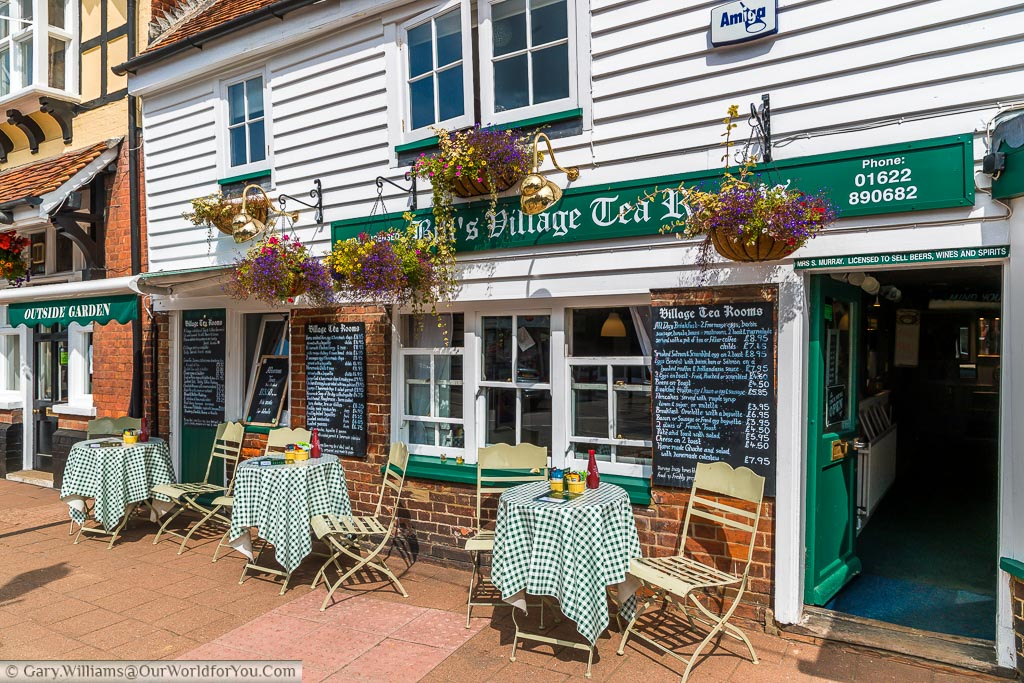 The village tea room shop with 3 tables and chairs outside covered in chequered tablecloths
