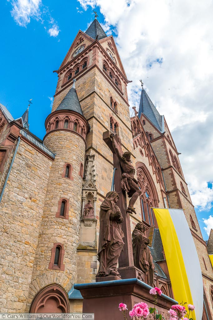 A portrait, wide angle view of a statue of Christ on the cross in front of the twin towers of the Cathedral of Bergstraße in Heppenheim.