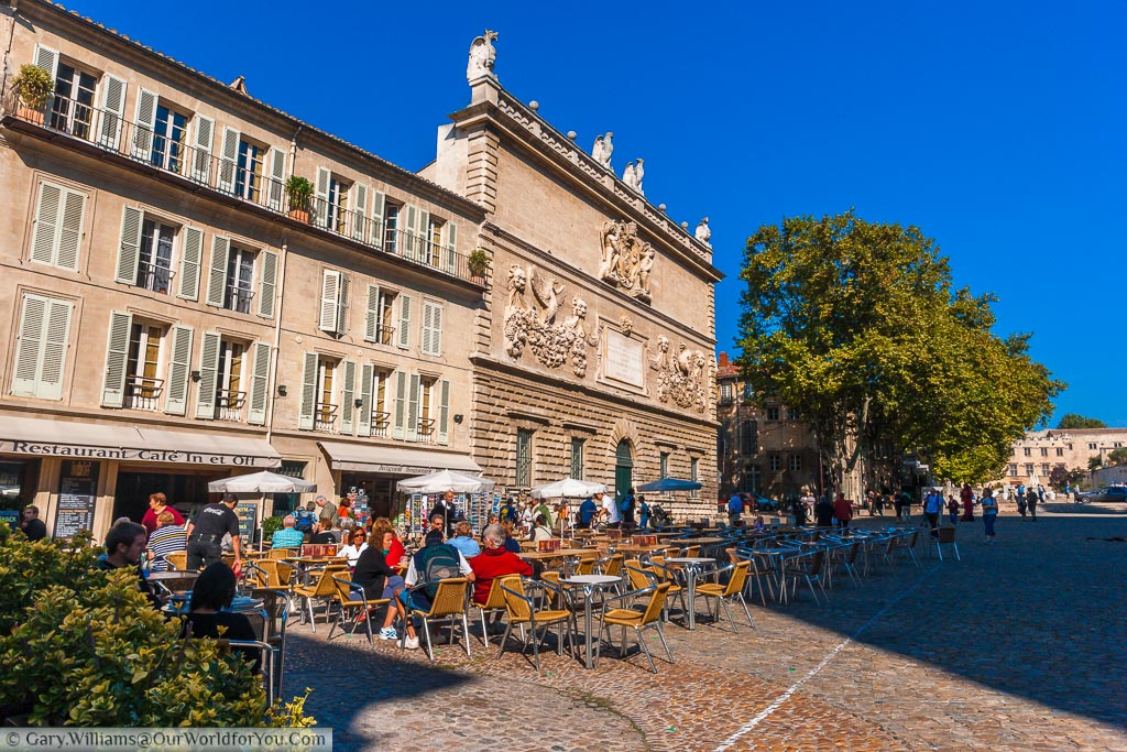 A cobbled street scene in Avignon, France, with tables and chairs lined up outside a cafe