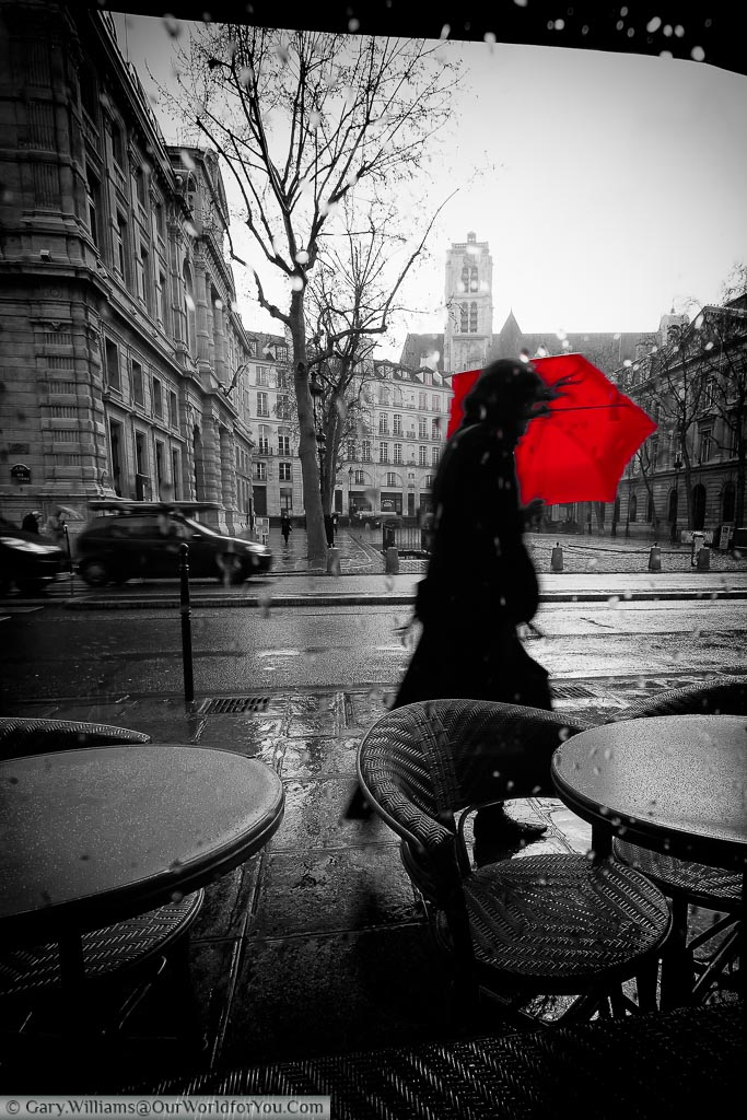 A black and white image, taken from inside a café, of a woman passing by with red umbrella, wrestling against the elements, on a stormy day in Paris