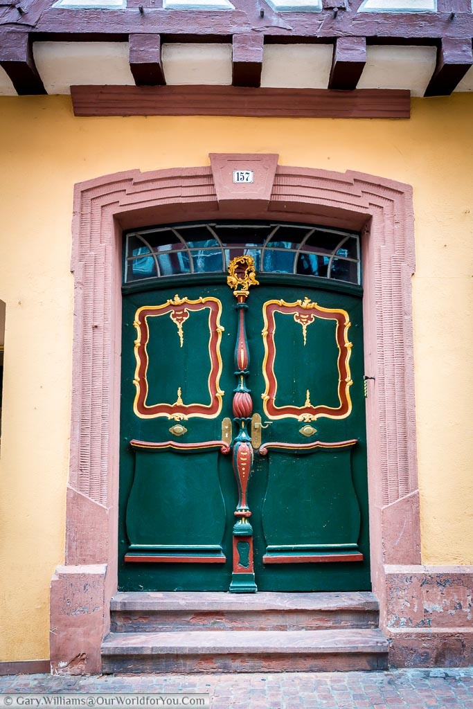 A closeup of an ornate green door within a stone door frame in Miltenberg