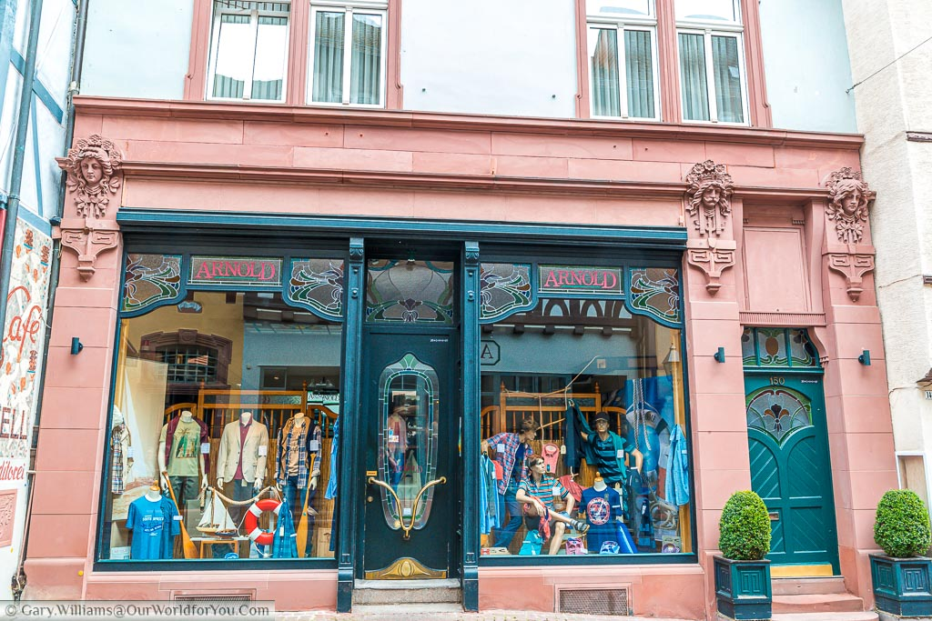 A red stone and blue steel art deco shop facade that is now an Outfitters.