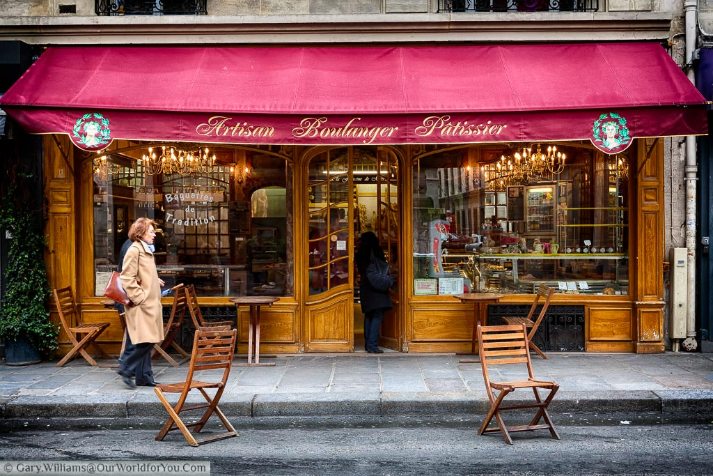 An elegant woman passing by I traditional artisan boulanger pâtissier on side road in Paris.  The front of the art deco styled shop is panelled in wood with 2 large windows displaying chandeliers inside, there is a deep burgundy canopy covering the upper portion of the store.