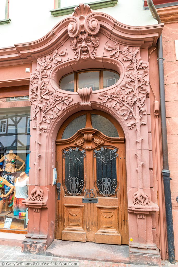 A wooden art deco door within a decorative red stone frame depicting nature.