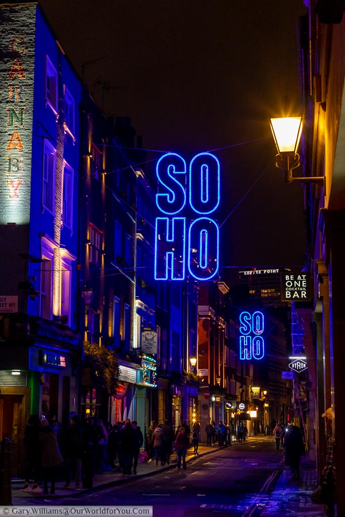 Looking along Beak Street after dark with blue neon signs indicating you're in Soho, and you're close to Carnaby Street.