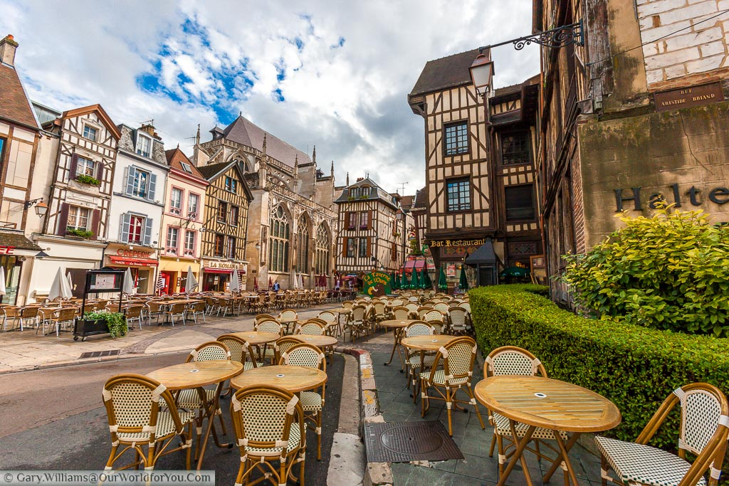 A view of a mass of tables and chairs on the pavement side of the historic city of Troyes. The backdrop is the half-timbered buildings synonymous with the region.