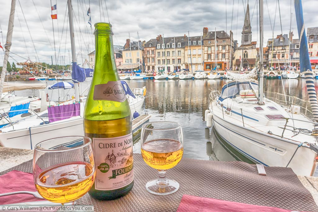 A bottle and 2 glasses of Cidre de Normandie served at the edge of the marina of Honfleur, filled with small sailing boats.