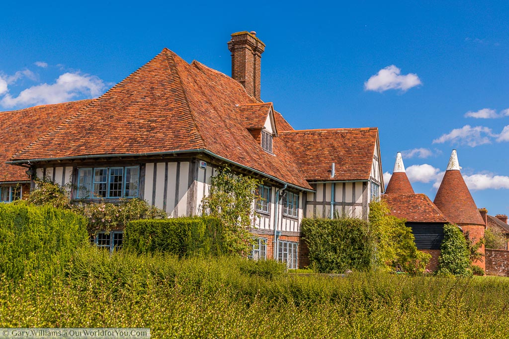 A typical Tudor era cloth hall half-timbered house alongside another symbol of Kent, the white topped oast houses in the village of Rolvenden, Kent