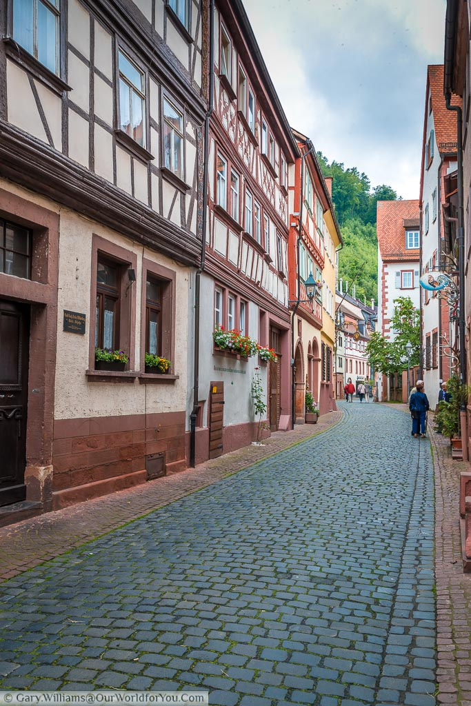 A cobbled street that runs through the centre of the Old Town of Miltenberg.  Either side are half-timbered traditional Bavarian buildings.