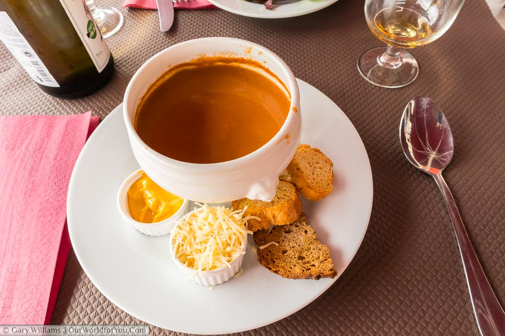 Traditional bowl of fish soup served with crispy croutons, grated hard cheese and a remoulade on the side