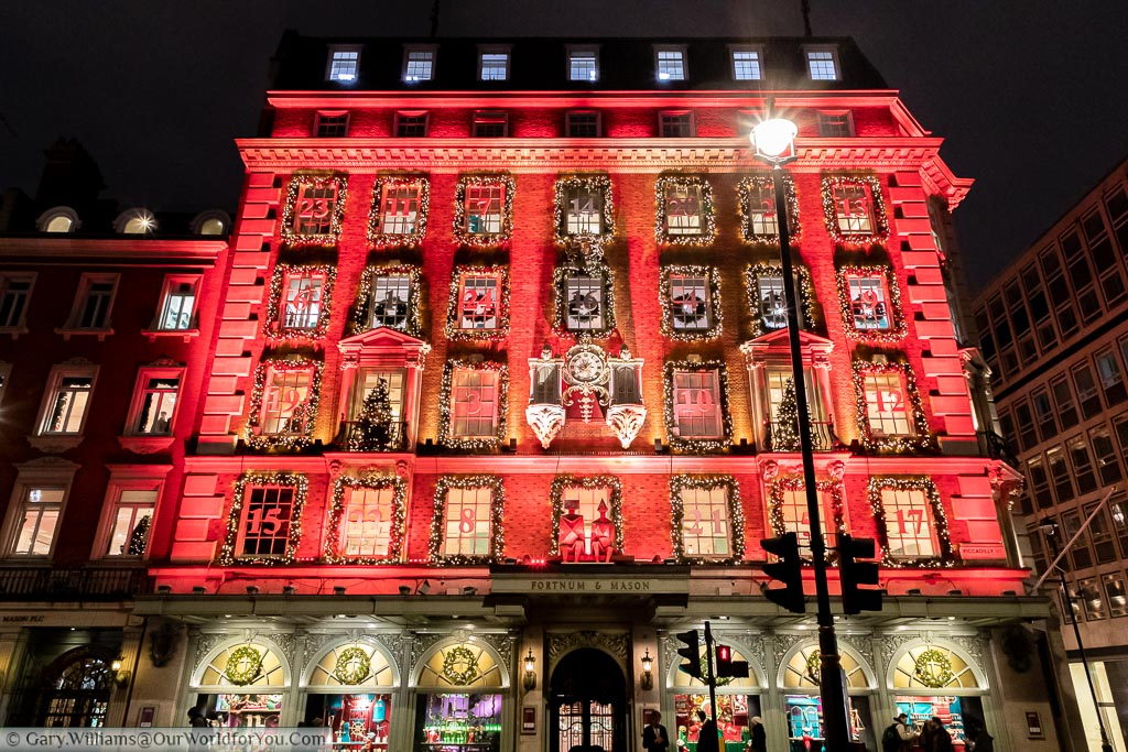 London's favourite food store, Fortnum & Mason's, decorated for Christmas as a giant advent calendar, illuminated in a festive red colour.
