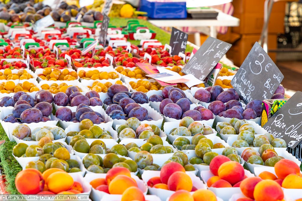 A fine selection of fresh softs fruit on market stall in Nice, France.  The stall is beautifully laid out with the bright colours of peaches, greengages, plums, kumquats and strawberries