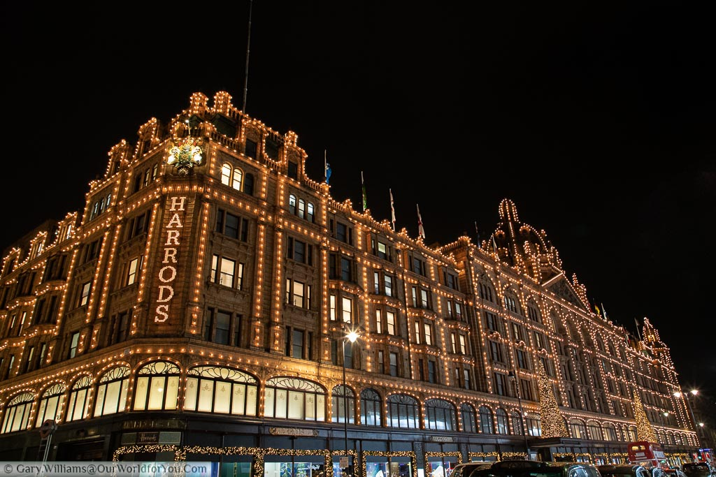 A side view of the Harrods Department store decorated with hundreds of small lights and a pair of Christmas trees above the main entrance.